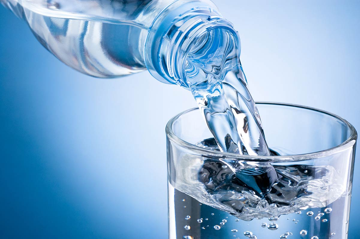 Clean drinking water pouring unto a glass tumbler from a plastic bottle